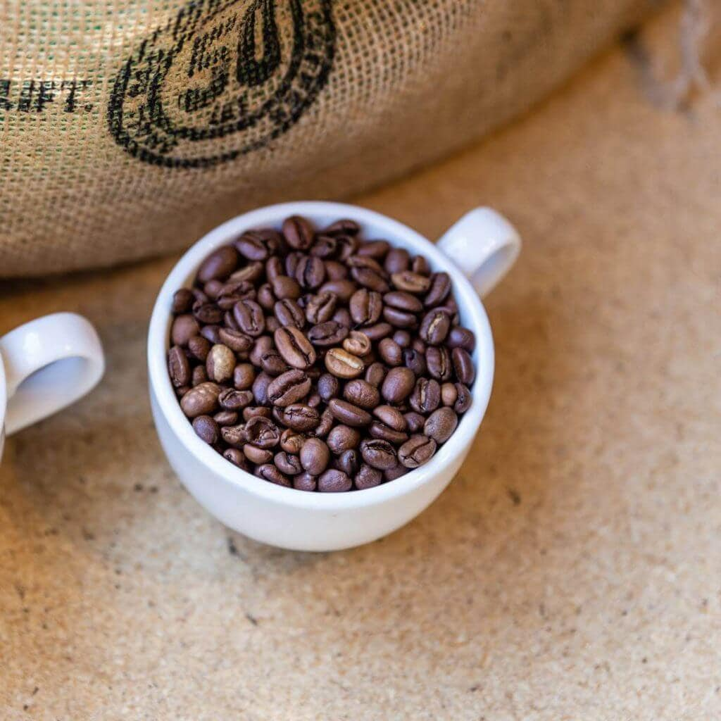 White coffee cup filled with whole coffee beans beside a burlap sack