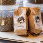 Two Cedar Grove Coffee House bags beside tubs of whole coffee beans