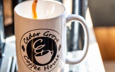 Black coffee being poured into a Cedar Grove Coffee House mug