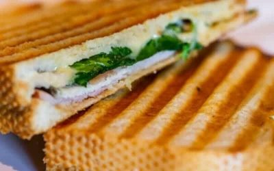 Ham and cheese panini cut in half on a white, square plate