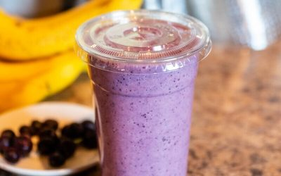 Blueberry smoothie sitting beside fresh blueberries and bananas